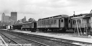 "MCRM coaches at Chicago (the yard south of Union Station) for filming of ""Gailey, Gailey"" a film on the life of Ben Hecht, portrayed by Beau Bridges. Coach at left is WC 63, at right is Soo Line 957. Ray Buhrmaster photo."