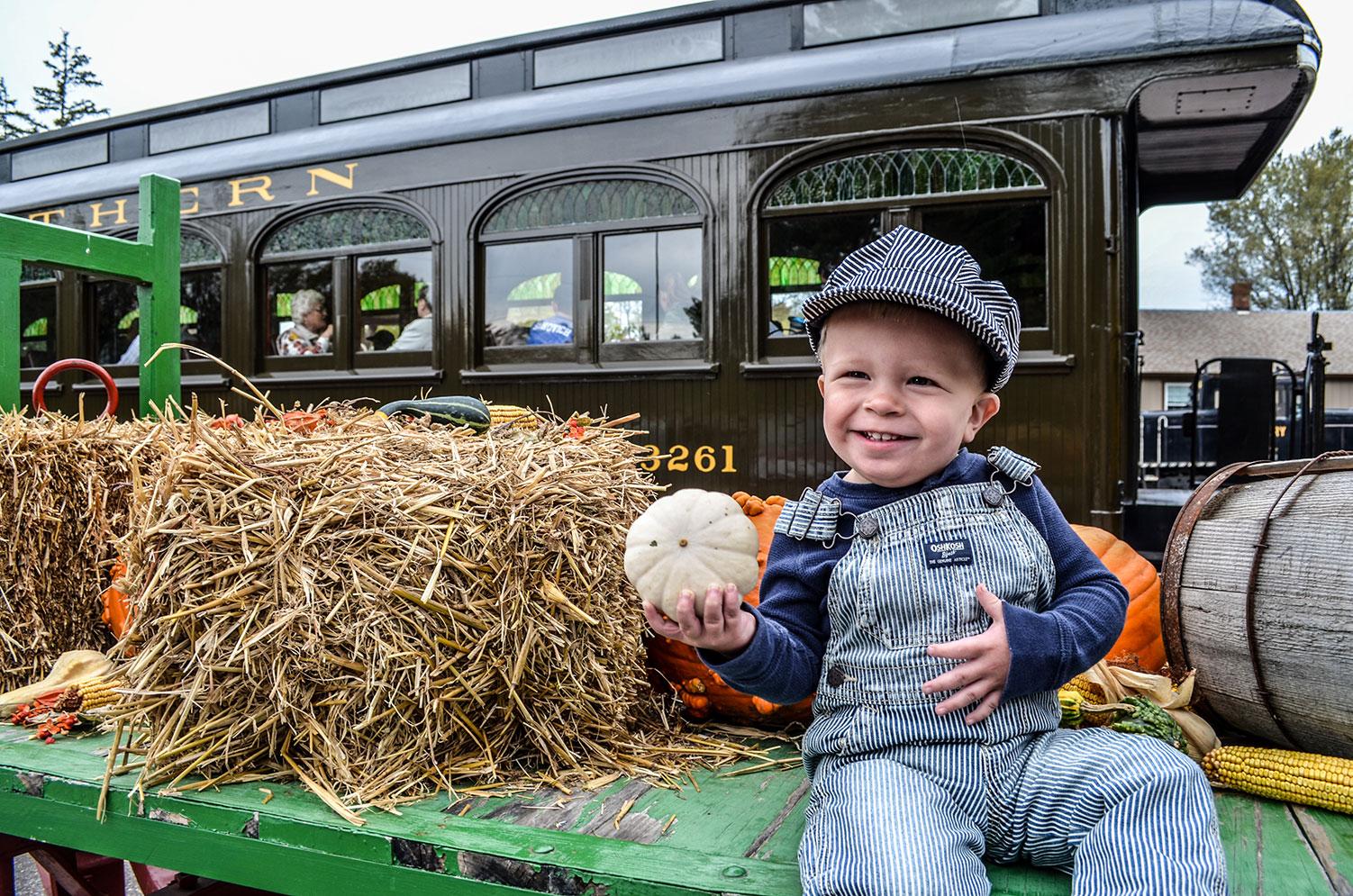 Child in engineer uniform holding gourd next to railroad passenger car
