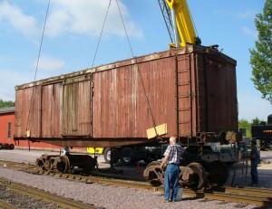 A crane unloads LS&I boxcar #2011