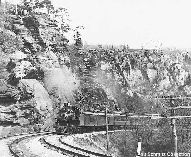 Back when C&NW's mainline between Madison and Elroy, Wisconsin was still double tracked, 4-4-2 #1027 guides a westbound passenger train of wooden varnish through the Ablemans narrows, some four miles west of North Freedom. C&NW 1027 was a Class D Atlantic built in December of 1901 by Schenectady and scrapped 39 years later, thereby making the number available for an incoming Alco S-2 diesel. Photo from the collection of Lou Schmitz.