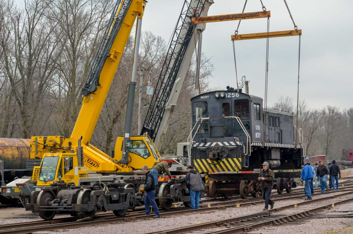 Two cranes lift the 60-ton MCRY #1256 to facilitate wheel removal. April  2018.