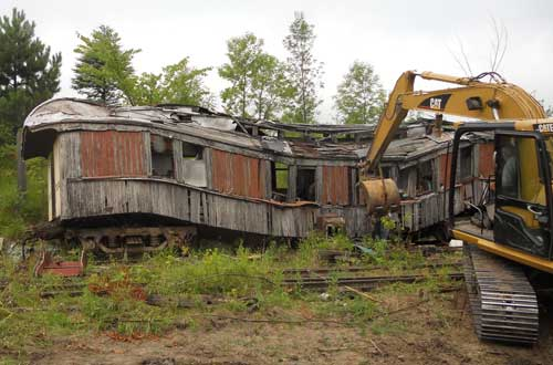 collapsed passenger railcar with excavator