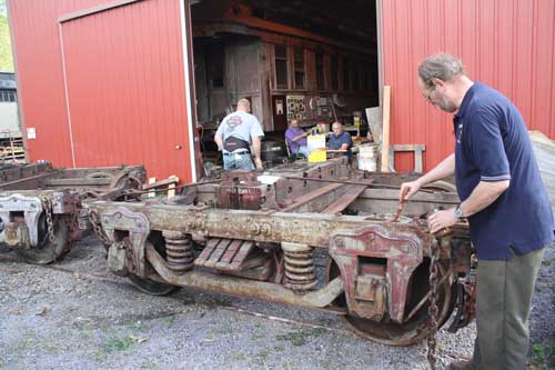 volunteer applying linseed oil to car trucks