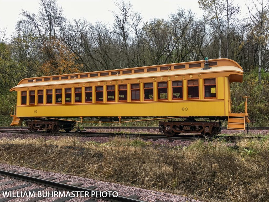 yellow and orange antique railroad passenger car with gold lettering that says Milwaukee Lake Shore & Western above windows and the number 63 near either end of the car